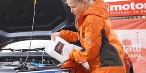 Lasol terva tuulilasinpesunestettä kaadetaan auton pesimeen.